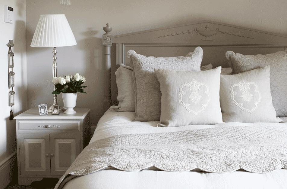 Modernes Landhausstil Schlafzimmer taupe Bett viele Kissen Nachttisch mit Leuchte