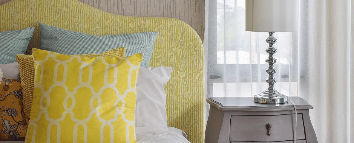 Schlafzimmer Bett gelbe Muster Kissen Nachttisch Taupe