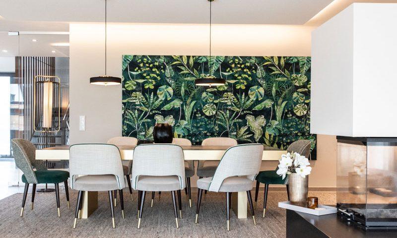 Essnereich mit Wandbilt dschugelmotiv goldener Tisch teppich und taupe Stühle Nussbaum