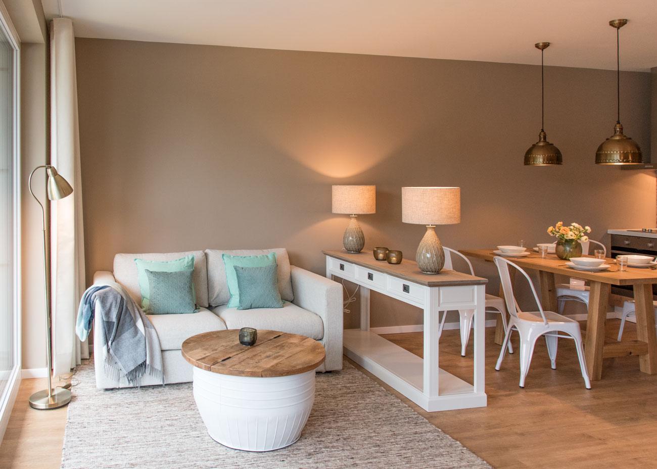 Ferienwohnung einrichten wohnen holztisch leuchten couch kissen konsole essbereich küche