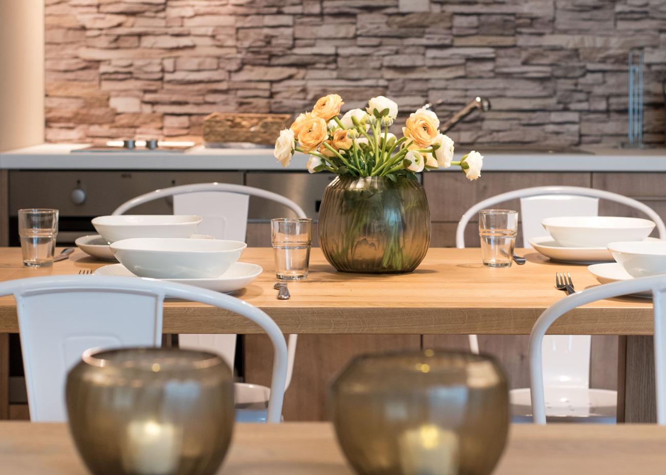 Ferienwohnung einrichten essentisch holz gedeckt mit stühlen weiss blumen vase