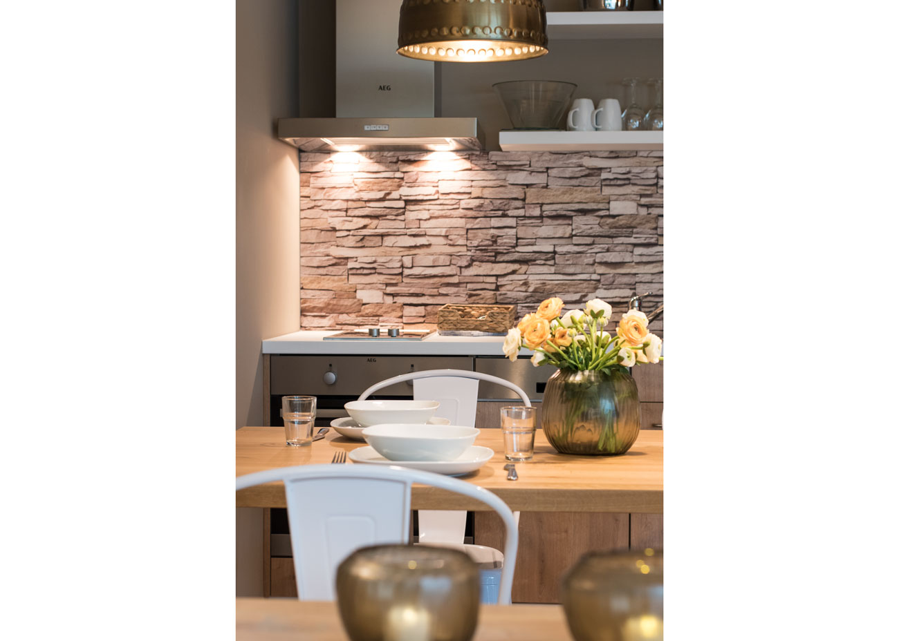 Ferienwohnung einrichten essentisch holz gedeckt mit stühlen weiss blumen vase steinwand küche