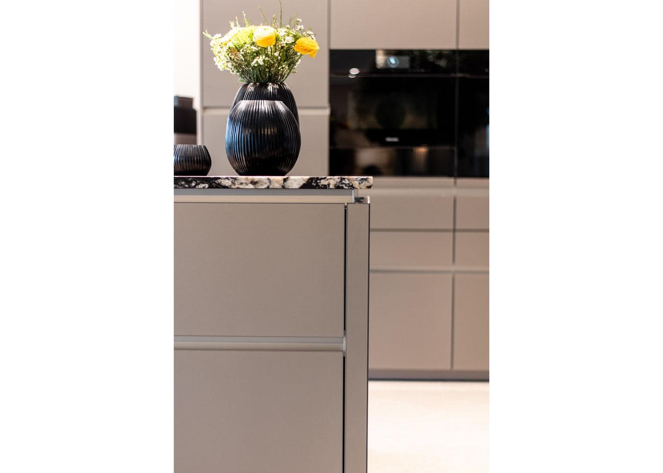 haus einrichten Küche glasfronten natursteinplatte detail kante mit vase