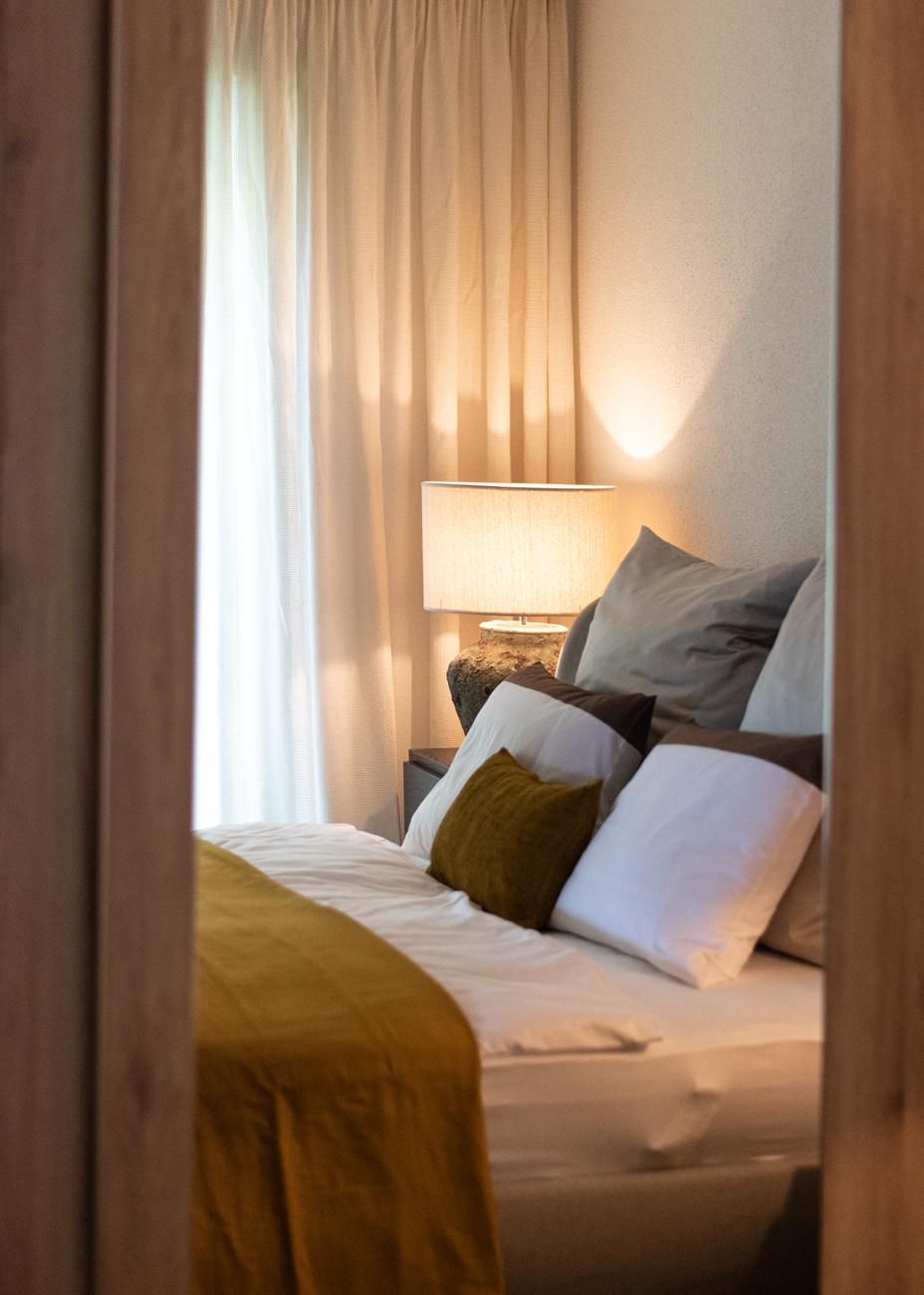 Schlafzimmer senfgelbe Akzente Tischleuchte gelbes Schlafzimmer Bett mit Kissendekoration Inneneinrichtung Ideen Einrichtungsideen Kundenprojekt Einrichtungskonzept Interior Design Räume planen